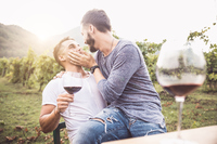 Küssendes Paar beim Wein trinken
